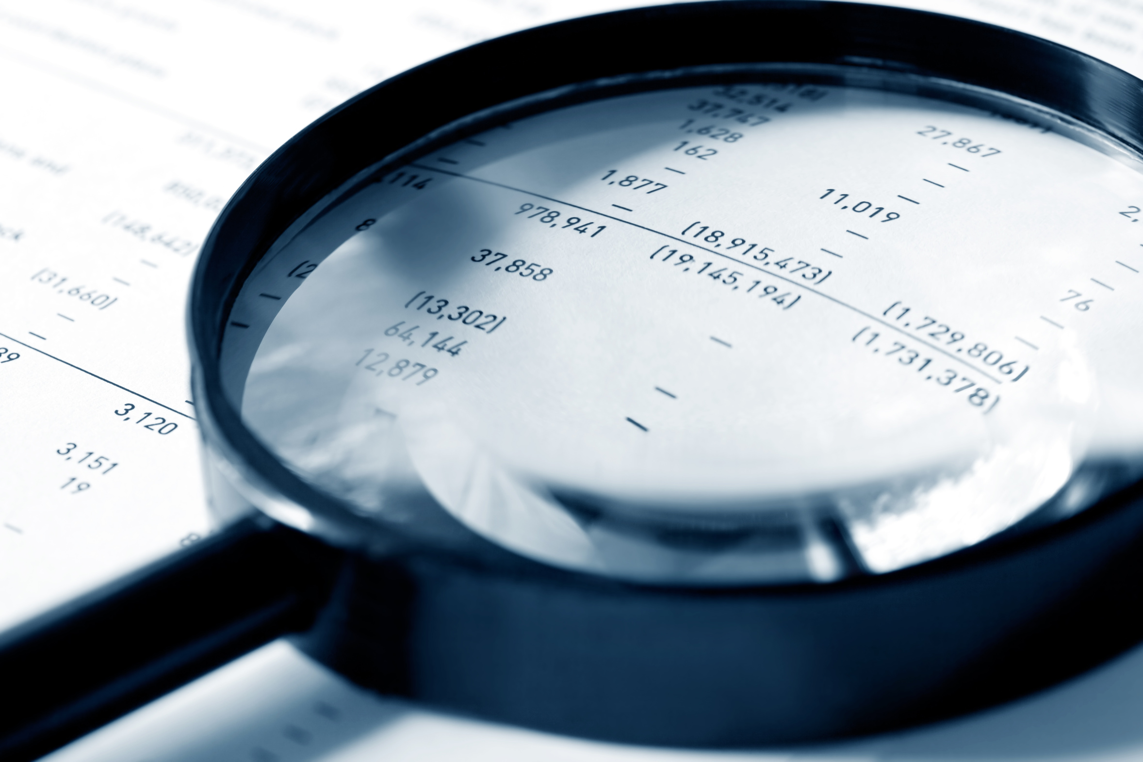 Magnifying glass over financial figures.  Shallow DOF, cyan tone.